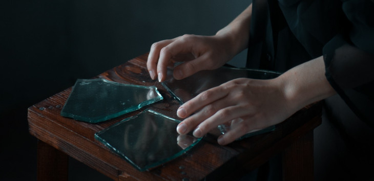 A woman's hands touch broken glass.